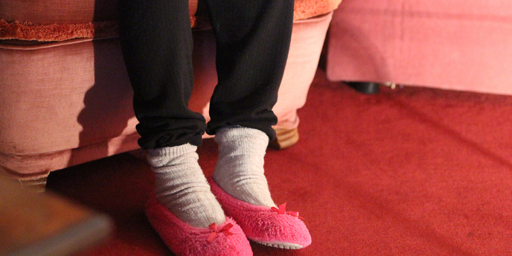 Die Bein einer Person in rosa Hausschuhen