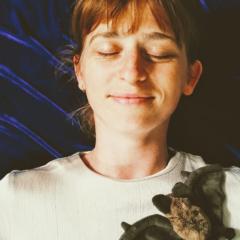Anne Bontemps liegend mit geschlossenen Augen und einem Kuscheltier auf der Schulter.