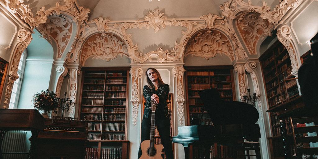 Foto von Sophie Chassee. Sie steht augestützt auf ihrer Gitarre in einer Bibliothek.in einer Biblio