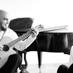 Wellington Barros an der Gitarre und Anne Bontems lachend vor einem Klavier