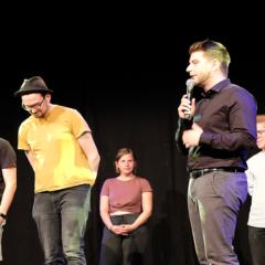 Verschiedene Poetry Slammer und der Moderator stehen auf der Bühne vor einem schwarzen Hintergrund.