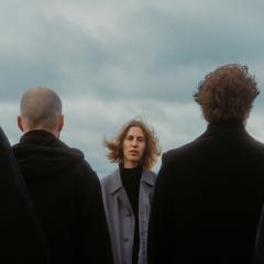 Bandphoto der Whispering Sons. Die Sängerin schaut in die Kamera. Die männlichen Mitglieder haben den Rücken zur Kamera gekehrt und sind ganz in schwarz angezogen.