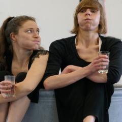 Zwei Frauen, die ein Wasserglas in der Hand halten und Wasser in den Backen haben.